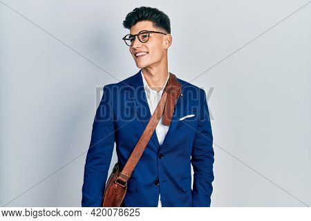 Young hispanic man wearing business clothes looking away to side with smile on face, natural expression. laughing confident.