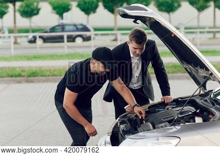 A Young Car Dealer In A Business Suit Shows Buyers A New Car. Young Man Buy A Car. Seller And Man In