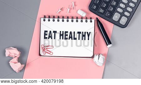 The Words Eat Healthy Written On A White Notebook. Closeup Of A Personal Agenda. Top View. Office Co