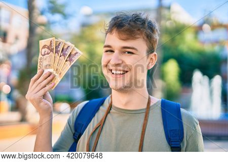 Young caucasian tourist man smiling happy holding hungarian forint banknotes at the city.
