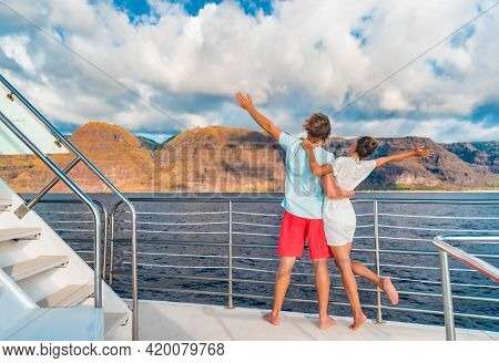 Couple on luxury yacht cruise ship tour at sunset feeling free happy with open arms in fun looking at mountain scenery. Romantic sunset boat ride watching view from deck on travel vacation.