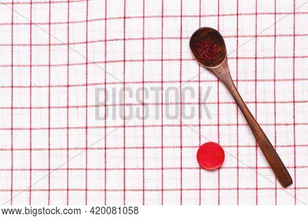 Saffron Background. Top View On Red Saffron Spice Threads Or Strands In A Rustic Wooden Spoon And A