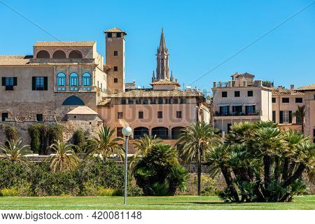 Old typical houses, medieval tower and gothic style belfry under blue sky in Palma de Mallorca, Spain.