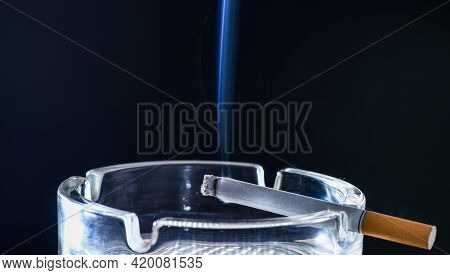 Burning Cigarette In Glass Ashtray. Smoke Rising From Cigarette In Ash-tray.