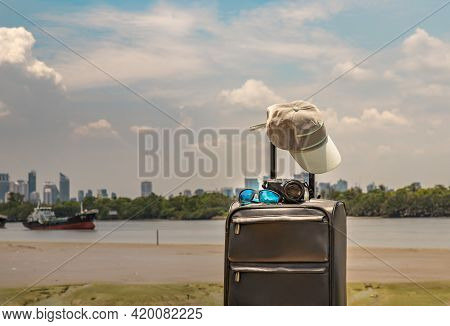 Vacation And Travel. Suitcase Or Luggage Bag With Cap, Photo Camera And Sun Glasses On Pier. Sky, Ri