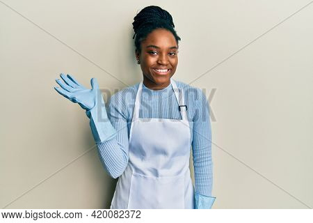 African american woman with braided hair wearing cleaner apron and gloves smiling cheerful presenting and pointing with palm of hand looking at the camera.
