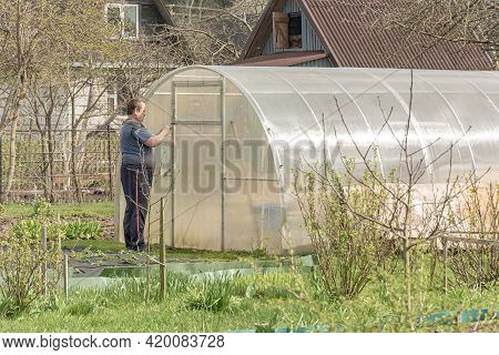 Poland, Lomza - May 01, 2021: A Farmer Opens A Greenhouse With Seedlings On A Private Farmstead. Sto