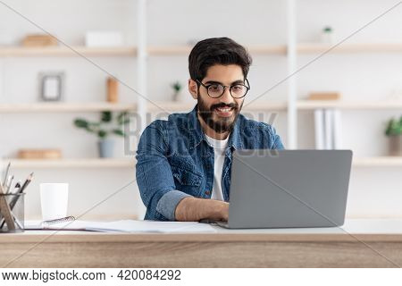 Freelance Work. Happy Arab Man Working On Computer At Home Office, Sitting At Workplace With Laptop,