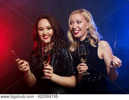 fashionable young women dressed in black cocktail dresses are singing with a microphone, holding disco balls, glasses of champagne and smiling