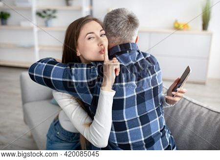 Beautiful Mature Woman Hugging Her Husband, Showing Hush Gesture, Having Secret Affair, Texting Her