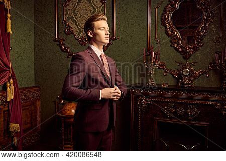 A portrait of a handsome blonde young man in a formal suit posing in a luxury apartments with classic interior. Men's beauty, fashion.