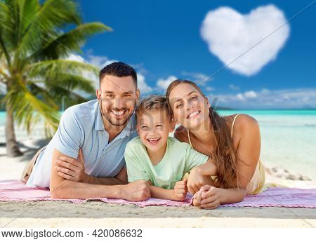 family, travel and tourism concept - happy mother, father and little son lying on blanket over tropical beach in french polynesia and heart shaped cloud on background