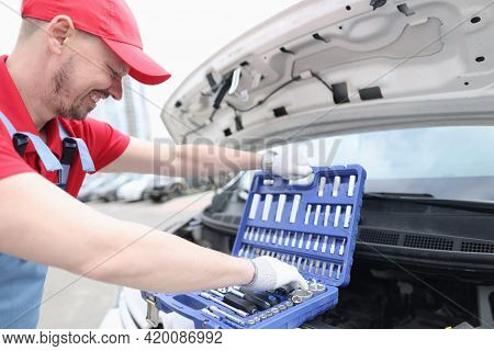 Man Repairman Taking Tools From Suitcase On Open Hood Of Car