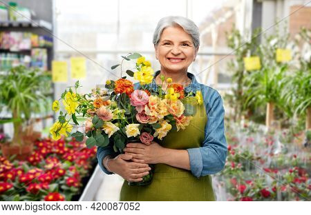 gardening, floristic and old people concept - portrait of smiling senior woman in green apron with bunch of flower over greenhouse at garden store on background