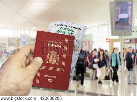 Hand Holding A Spain Passport With A Wrinkled Paper Coronavirus Covid 19 Immunity Certificate Blurre