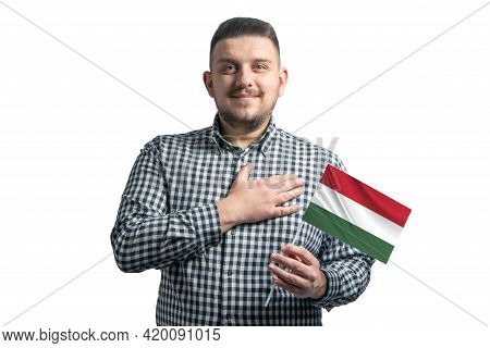White Guy Holding A Flag Of Hungary And Holds His Hand On His Heart Isolated On A White Background W