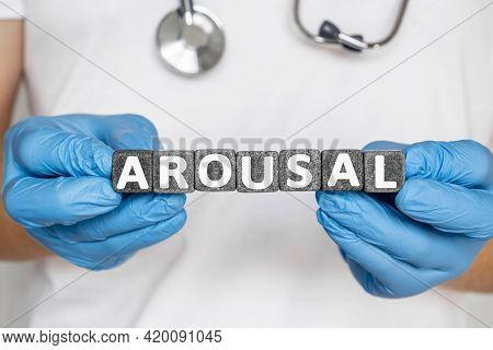 Arousal - Word From Stone Blocks With Letters Holding By A Doctor's Hands In Medical Protective Glov