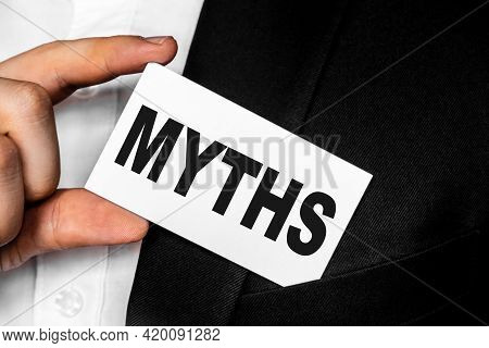 Inscription Myths On A White Business Card. A Man In A Black Business Suit Lowers Or Removes From Hi