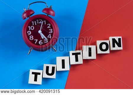 Tuition - Word On Wooden Cubes On A Multi-colored Background With An Alarm Clock. Info Concept