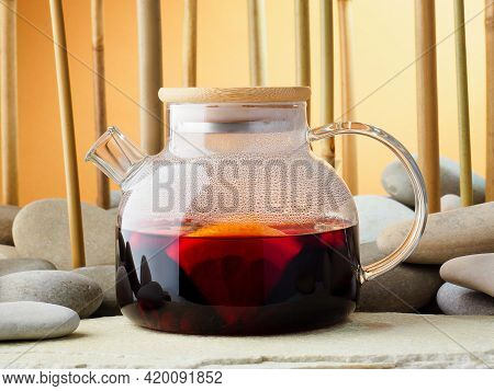 Glass Teapot With Hot Red Berry Tea Karkade, Close-up. Tea On The Background Of A Bamboo Grove And S