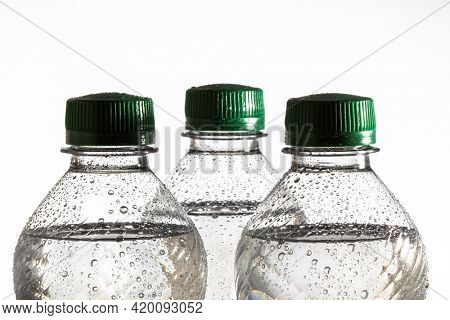Three water bottle close up with water drops on white background