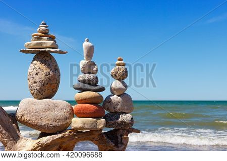 Three Rock Zen Pyramid Of Balanced Stones On A Background Of The Summer Sea And Blue Sky. Concept Of