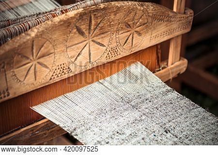 Closeup Of An Old Hand-weaving Vintage Wooden Loom Being Used To Make Fabric. Traditional European S