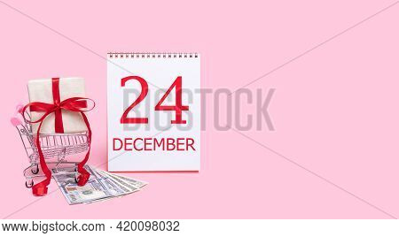 24th Day Of December. A Gift Box In A Shopping Trolley, Dollars And A Calendar With The Date Of 24 D