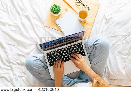 Blonde Woman Working At Home Office. Happy Beautiful Lady Girl Typing At Laptop, Sits On Bed With Co