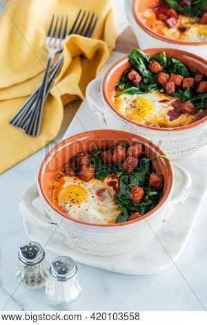 Baked Eggs In Soup Crocks With Sauteed Spinach And Chorizo Sausage, Ready For Eating.