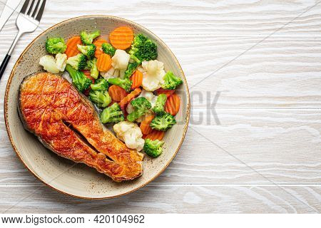 Healthy Fish Dinner: Grilled Salmon Fish Steak With Vegetables Salad On Ceramic Plate With Fork And