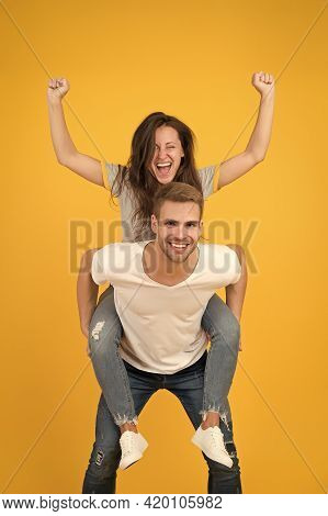 Solid Support. Cheerful Man Piggybacking His Girlfriend. Hipster Giving Sexy Woman Piggyback Ride. H