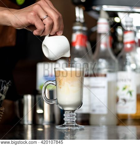 Making Latte Coffee. Barista Pours Freshly Brewed Coffee Into Whipped Milk Froth In Front Of Bottles