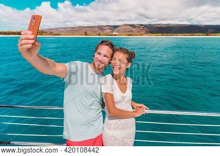 Cruise selfie vacation happy tourists taking photo with phone on boat trip ferry. Interracial couple Asian woman, Caucasian man.