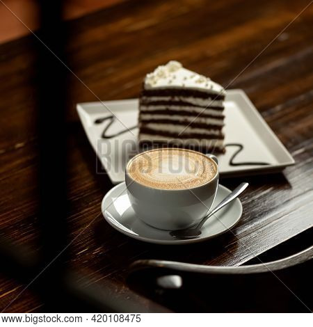 Cup Of Creamy Cappuccino Coffee. Portion Of Hot Aromatic Drink With Slice Of Cake On Dark Wooden Tab
