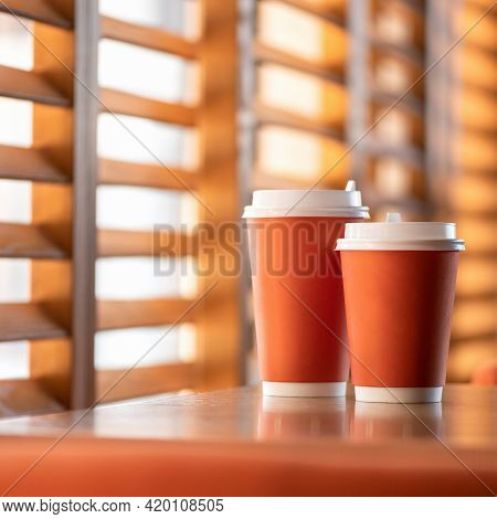 Mockup Of Blank Paper Cup. Coffee Drink In Paper Cups On Table. Two Orange Disposable Cardboard Cups