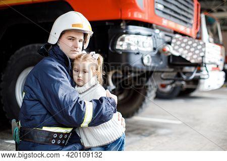 Brave Firefighter In Uniform Holding Little Saved Girl Standing On Black Background.