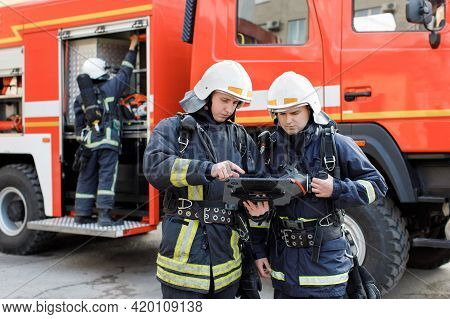 Portrait Of Two Firefighters In Fire Fighting Operation, Fireman In Protective Clothing And Helmet U