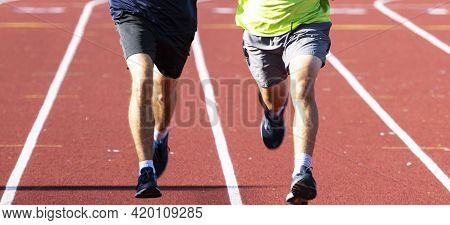 Close Up Of The Legs Of Two High School Boys Running Side By Side In Lanes On A Red Track In Bright