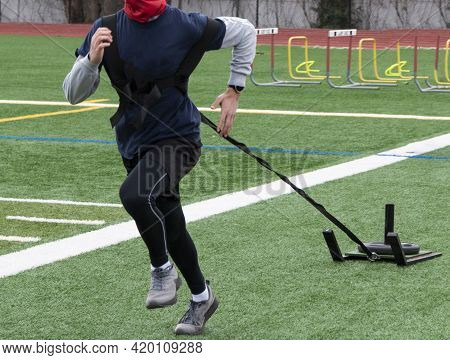 Front View Of A High School Buy Running With A Weighted Sled Strapped To Him Dragging It Behind Him
