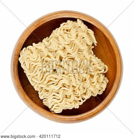 Dried Instant Noodles In A Wooden Bowl. Instant Ramen Are Noodles Sold In Precooked And Dried Block