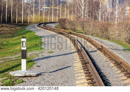 An Empty Winding Narrow-gauge Railway Along Which Young Birches Grow. Multi-storey Residential Build