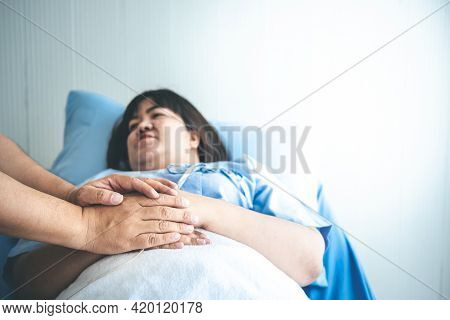 Close Up Hand Of Husband Holding Hand His Wife To Encourage, She Is  Illness Lying In A Patient's Be