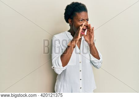 Young african american girl wearing casual clothes shouting angry out loud with hands over mouth