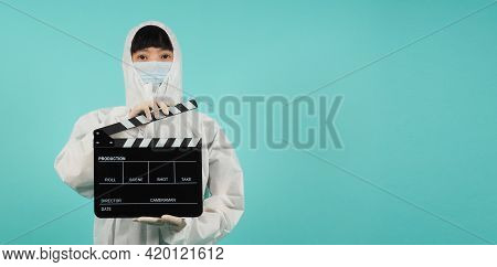 Black Clapperboard Or Movie Slate.asian Woman Wear Face Mask And Ppe Suit On Mint Green Or Tiffany B