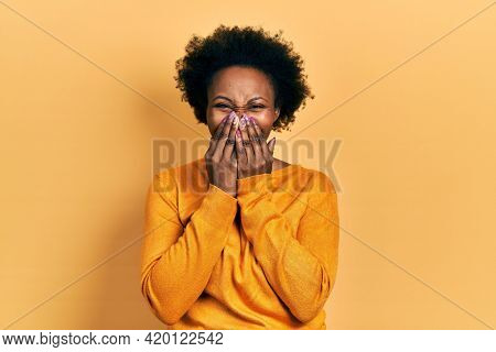 Young african american woman wearing casual clothes laughing and embarrassed giggle covering mouth with hands, gossip and scandal concept