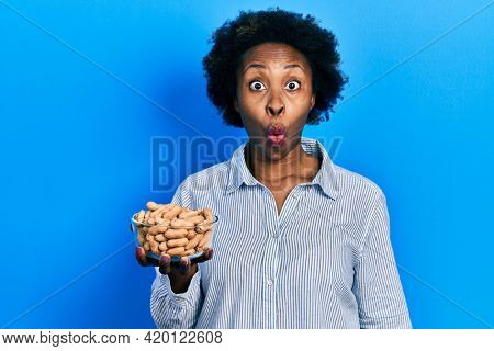Young african american woman holding peanuts scared and amazed with open mouth for surprise, disbelief face