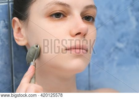 Portrait Of Young Woman Massaging Skin With Face Jade Roller Massager. She Is Relaxing Lying In Bath