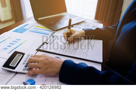 Accountant Women Calculate And Writing Contract Documents On The Table With Statistic Paper, Laptop,