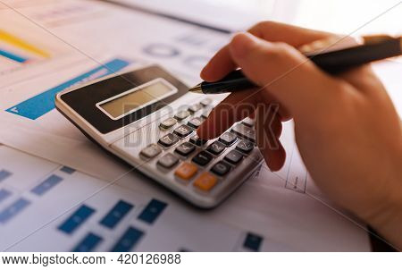 Close Up, Hand Holding Pen And Press Calculator To Calculate Expenses, Accounting, Financial. Backgr